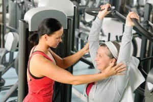 Personal trainer helping an older adult woman with a resistance training exercise.