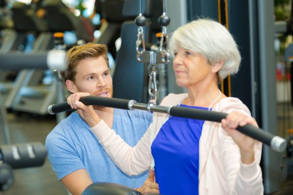 Male senior fitness specialist working with older female client.