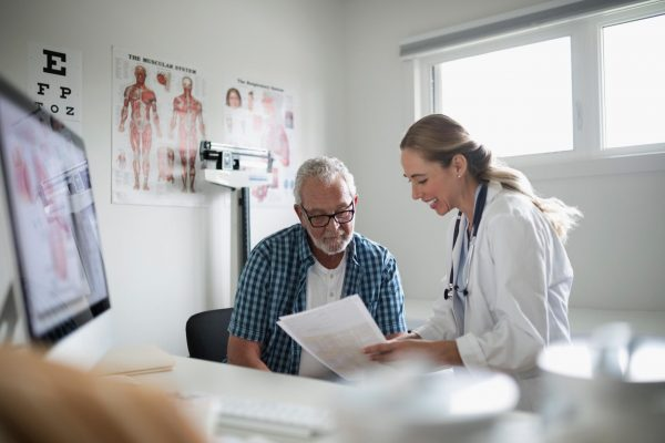 Woman physician working with an older patient who might be referred to a senior fitness specialist.