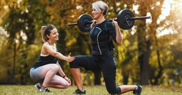 Senior fitness trainer with woman client